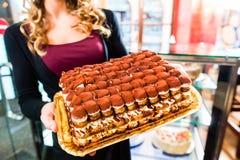 Женский хлебопек представляя торт в кондитерскае Стоковое Изображение RF