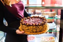 Женский хлебопек представляя торт в кондитерскае Стоковые Фотографии RF