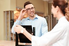 Женский человек порции офтальмолога для того чтобы выбрать стекла стоковые изображения