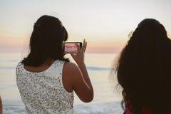 Женский человек фотографируя сотового телефона красивый горизонт океана на заходе солнца стоковые изображения