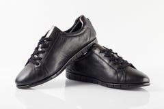 Женский черный кожаный ботинок на белой предпосылке Стоковое Фото