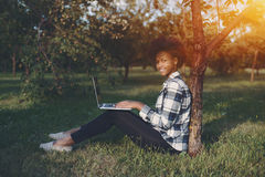 Женский черный студент с компьтер-книжкой в парке Стоковое фото RF