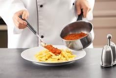 Женский шеф-повар добавляя bolognese соус к очень вкусным макаронным изделиям стоковое изображение rf