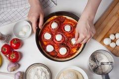 Женский шеф-повар добавляет сыр к моццарелле для того чтобы сделать домодельную пиццу На белой таблице моццарелла, тесто пиццы, и стоковое фото rf