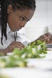 Женский шеф-повар подготавливая салат в кухне стоковое изображение rf