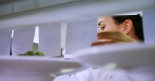 Женский шеф-повар смотря список заказа в коммерчески кухне 4k видеоматериал