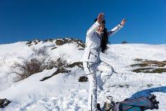Женский лыжник изменяя в ботинки лыжи на горном склоне Стоковая Фотография