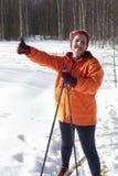 Женский лыжник по пересеченной местностей дает большие пальцы руки вверх по знаку Стоковое Изображение