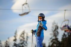 Женский лыжник против лыж-подъема и лес на солнечный день Стоковая Фотография