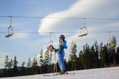 Женский лыжник против лыж-подъема и лес на солнечный день Стоковое Изображение RF