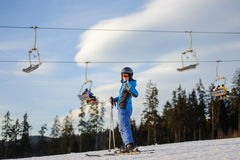 Женский лыжник против лыж-подъема и лес на солнечный день Стоковая Фотография RF