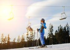 Женский лыжник против лыж-подъема и лес на солнечный день Стоковые Фотографии RF