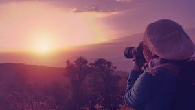 Женский backpacker принимая фотоснимок на заход солнца в утре Стоковые Фото