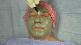 Женский beautician в перчатках кладет дальше сторону мужского клиента маска грязи с щеткой акции видеоматериалы