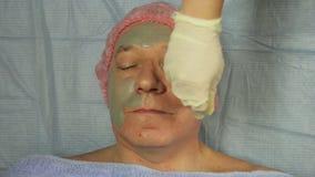 Женский beautician в перчатках кладет дальше сторону человека маска грязи сток-видео
