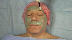 Женский beautician в перчатках кладет дальше сторону человека маска грязи видеоматериал