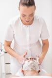 Женский beautician проходя лицевую обработку Стоковая Фотография