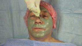 Женский cosmetologist в перчатках прикладывает маску грязи на стороне мужчины clien видеоматериал