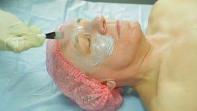 Женский cosmetologist в перчатках прикладывает маску обработки к стороне человека s с щеткой Взгляд со стороны акции видеоматериалы