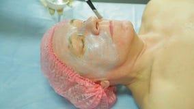 Женский cosmetologist в перчатках прикладывает маску обработки к стороне человека s с щеткой видеоматериал
