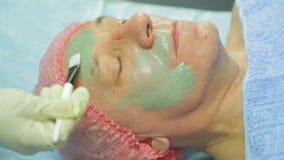 Женский cosmetologist в перчатках прикладывает терапевтическую маску глины к стороне человека s с щеткой сток-видео