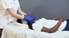 Женский cosmetologist делая ослабляя массаж к женскому африканскому клиенту сток-видео