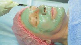 Женский cosmetologist прикладывает заживление маску грязи к стороне человека s с щеткой Взгляд со стороны сток-видео