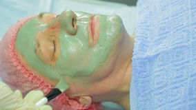 Женский cosmetologist прикладывает заживление маску грязи к стороне человека s с щеткой Взгляд со стороны акции видеоматериалы