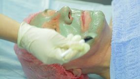 Женский cosmetologist прикладывает заживление маску грязи к стороне человека s с щеткой акции видеоматериалы