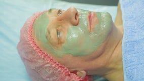 Женский cosmetologist прикладывает маску грязи к стороне человека s с щеткой Взгляд со стороны сток-видео
