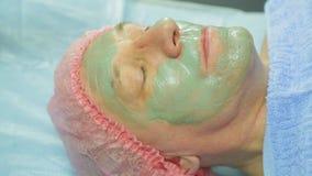 Женский cosmetologist прикладывает маску грязи к стороне человека s с щеткой Взгляд со стороны видеоматериал