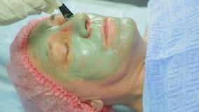 Женский cosmetologist прикладывает маску грязи к стороне человека s с щеткой акции видеоматериалы