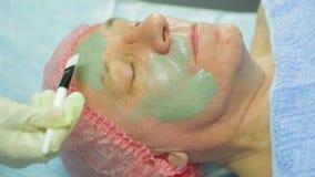 Женский cosmetologist прикладывает маску грязи к стороне man's с щеткой видеоматериал