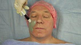 Женский cosmetologist прикладывает маску грязи на стороне человека сток-видео