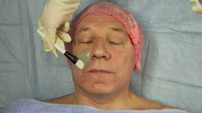 Женский cosmetologist прикладывает маску грязи на стороне человека акции видеоматериалы
