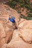 Женский hiker взбираясь крутая красная скала утеса Стоковые Изображения RF