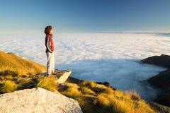 Женский hiker достигая ее цель на верхней части горы и смотря величественный панорамный взгляд итальянских западных Альпов с обла Стоковое Изображение RF
