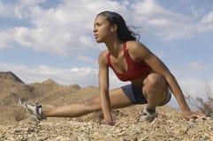 Женский Jogger протягивая в горах Стоковая Фотография RF