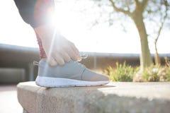 Женский jogger связывая ее шнурки ботинка Стоковое Изображение