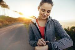 Женский jogger смотря ее дозор идя на улицу стоковые изображения