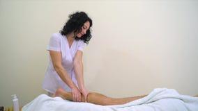 Женский masseur используя масло ароматности для moisturing ноги человека для массажировать видеоматериал