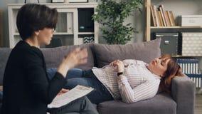 Женский psychotherapist давая совет подавленному брюзгливому пациенту лежа на софе сток-видео