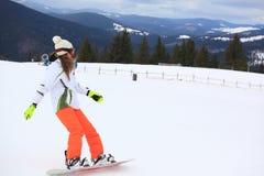 Женский snowboarder на наклоне горы Стоковые Изображения RF