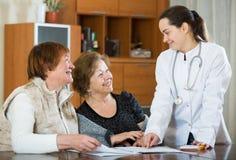 Женский therapeutist советуя с старшими пациентами в клинике Стоковая Фотография RF