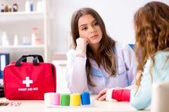 Женский traumatologist доктора перевязывая женского пациента стоковое фото