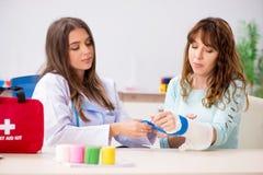 Женский traumatologist доктора перевязывая женского пациента стоковые изображения