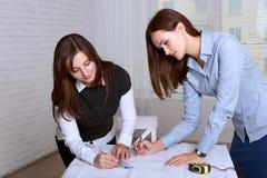 2 женских архитектора изучая зоны светокопий Стоковое фото RF