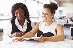 2 женских архитектора работая совместно на столе в офисе Стоковая Фотография RF