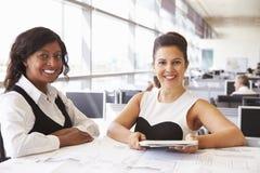 2 женских архитектора работая совместно, смотрящ к камере Стоковое Фото