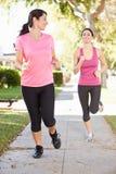 2 женских бегуна работая на пригородной улице Стоковые Фотографии RF